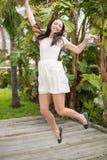 Mooi omhoog en brunette die springen glimlachen Stock Afbeeldingen