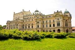 Mooi oud die paleis door bloeiend groen tegen de hemel wordt omringd stock foto's