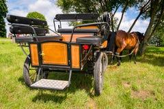 Mooi oud vervoer op het gras met paarden die hooi eten Royalty-vrije Stock Afbeeldingen