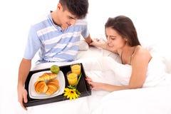 Mooi paar dat ontbijt heeft dat in het bed ligt stock afbeelding