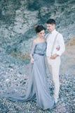 Mooi paar dichtbij de rotsen, op het overzees, geknuffel die, het lachen, huwelijk neer eruit zien royalty-vrije stock fotografie