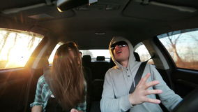 Mooi paar die in de auto bij zonsondergang dansen stock footage