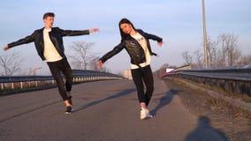 Mooi paar die in de ochtend op de weg aan de stad, langzame motie dansen stock footage