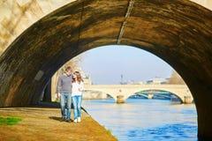 Mooi paar die in Parijs door de Zegen lopen Royalty-vrije Stock Afbeeldingen