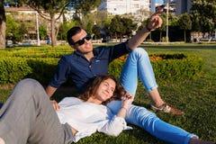 Mooi paar die in park rusten Royalty-vrije Stock Afbeeldingen