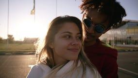 Mooi paar die terwijl status in openlucht op de parkerenstreek koesteren Afrikaanse man en het Kaukasische vrouw bevindende emrac stock footage
