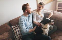 Mooi paar die thuis en van hun hond ontspannen houden royalty-vrije stock foto