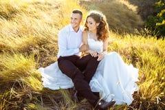 Mooi paar in gebied, Minnaars of jonggehuwde het stellen op zonsondergang met perfecte hemel Stock Foto