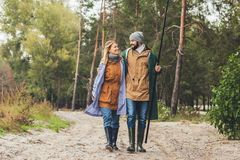 mooi paar in regenjassen met staven het gaan stock foto