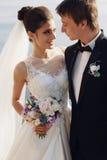 Mooi paar schitterende bruid in huwelijkskleding het stellen met elegante bruidegom op overzeese kosten Stock Foto's