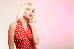 Mooi pinupmeisje in blonde pruik en retro rode kleding die een kus blazen. Royalty-vrije Stock Foto