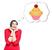 Mooi plus groottevrouw die in rode kleding over cake dromen stock foto's