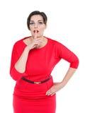 Mooi plus groottevrouw in rode kleding met vinger op lippenisola Stock Afbeeldingen