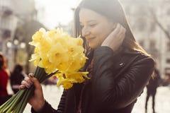 Mooi portret die van donkerbruine vrouw gele de lentebloemen houden royalty-vrije stock afbeeldingen