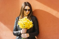 Mooi portret die van donkerbruine vrouw gele de lentebloemen in zonnige dag houden stock fotografie