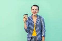 Mooi portret die van positief met korte haar jonge vrouw rusten in gestreept kostuum die, het drinken koffie met toothy glimlach  royalty-vrije stock foto's