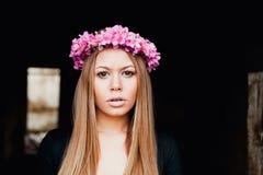 Mooi portret van een blondemeisje met een roze kroon van bloemen Royalty-vrije Stock Afbeeldingen