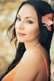 Mooi portret van een jonge donkerbruine vrouw met oranje bloem in haar haar Royalty-vrije Stock Afbeelding