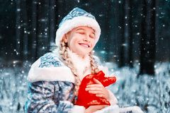 Mooi portret van het sneeuwmeisje in een feestelijk kostuum het gelukkige meisje houdt nieuwe jaarzak met giften De fabelachtige  royalty-vrije stock afbeeldingen
