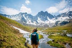 Mooi reizend meisje die zich bovenop berg bij zonsondergang bevinden en mobiele telefoon met behulp van royalty-vrije stock foto