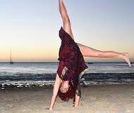 Mooi rijp brunette die cartwheel op het strand doen royalty-vrije stock afbeelding