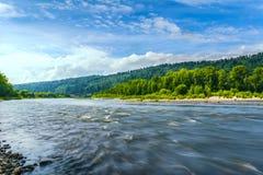 Mooi rivierlandschap met bewolkte blauwe die hemel in wordt weerspiegeld Stock Foto's