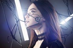 Mooi robotmeisje die in cyberpunkstijl omhoog op achtergrond van draden en gloeiende lampen kijken royalty-vrije stock afbeelding