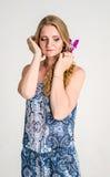 Mooi romantisch meisjesblonde in de zomerkleding met orchideebloem Royalty-vrije Stock Foto's