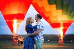 Mooi romantisch paar die bij weide koesteren hete luchtballon op een achtergrond royalty-vrije stock afbeeldingen