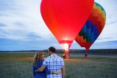Mooi romantisch paar die bij weide koesteren hete luchtballon op een achtergrond royalty-vrije stock foto