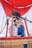 Mooi romantisch paar die bij weide koesteren hete luchtballon op een achtergrond royalty-vrije stock foto's