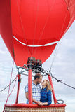 Mooi romantisch paar die bij weide koesteren hete luchtballon op een achtergrond stock fotografie