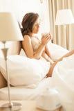 Mooi romantisch vrouwenbrunette die op het bed in haar ruimte thuis liggen Stock Foto's