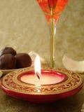 Mooi rood kaars en glas, snoepjes op een achtergrond Stock Afbeelding