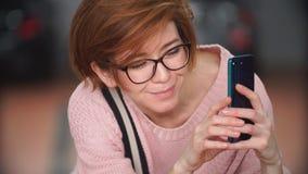 Mooi roodharig meisje die beelden op een werktuigkundige van de smartphonebaan nemen stock footage
