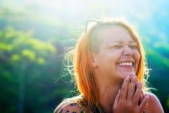 Mooi roodharig meisje die met geschoren tempels met geluk tegen de achtergrond van bergen lachen stock foto