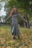 Mooi roodharig meisje die zich dichtbij een boom in de herfst bevinden Royalty-vrije Stock Foto