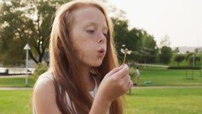 Mooi roodharig meisje met sproeten die op paardebloem in park blazen stock videobeelden