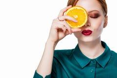 Mooi roodharigemeisje met sinaasappel stock foto's