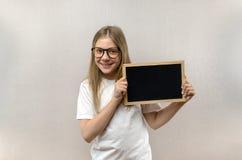 Mooi schadelijk meisje die met glazen een teken in haar handen houden Exemplaar-ruimte stock afbeelding