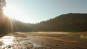 Mooi schilderachtig Synevir-meer op prachtige zonsondergang Adembenemend Karpatisch bergen en paar die in liefde lopen stock videobeelden