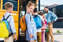 mooi schoolmeisje die camera bekijken terwijl status dichtbij schoolbus met klasgenoten stock afbeeldingen