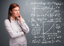 Mooi schoolmeisje die over complexe wiskundige tekens denken Stock Foto