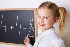 Mooi schoolmeisje die zich dichtbij bord met krijtje en het glimlachen bevinden Stock Foto's