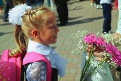 Mooi schoolmeisje met een boeket van bloemen terug naar school Stock Afbeeldingen