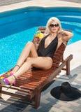 Mooi sensueel blonde die met modieuze zonnebril bij zwembad met een sap ontspannen Aantrekkelijke lange eerlijke haarvrouw royalty-vrije stock afbeeldingen
