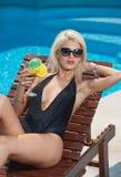 Mooi sensueel blonde die met modieuze zonnebril bij zwembad met een sap ontspannen Aantrekkelijke lange eerlijke haarvrouw stock foto's