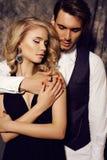 Mooi sensueel paar in elegante kleren die in studio stellen Royalty-vrije Stock Afbeelding