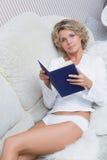 Mooi sexy blondemeisje die een boek lezen die liggen stock afbeelding