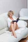 Mooi sexy blondemeisje die een boek lezen die liggen stock foto's